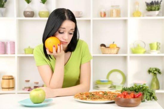 девушка на кухне с апельсином в руке